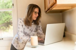 Woman using gray laptop computer in kitchen