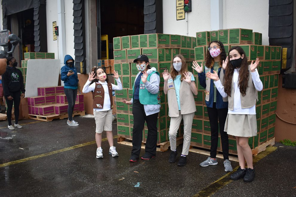Group of Girl Scouts in front of boxes of cookies