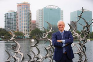 Dick Batchelor standing in front of lake eola in Orlando Florida
