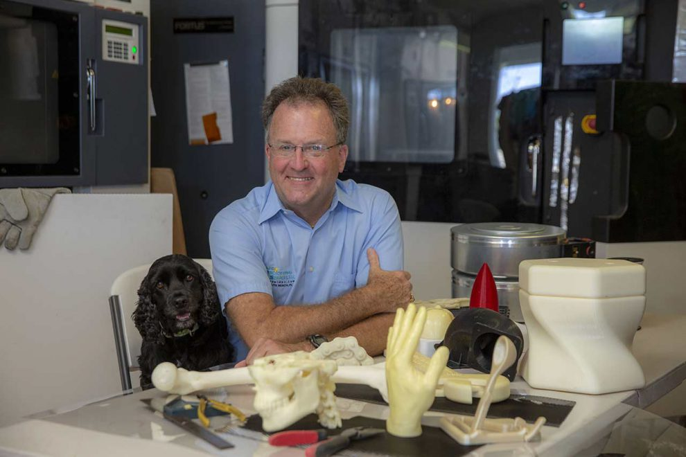 Ken Brace sitting with his small black dog at a table full of3d prototyped objects such as a hand and femur bone.