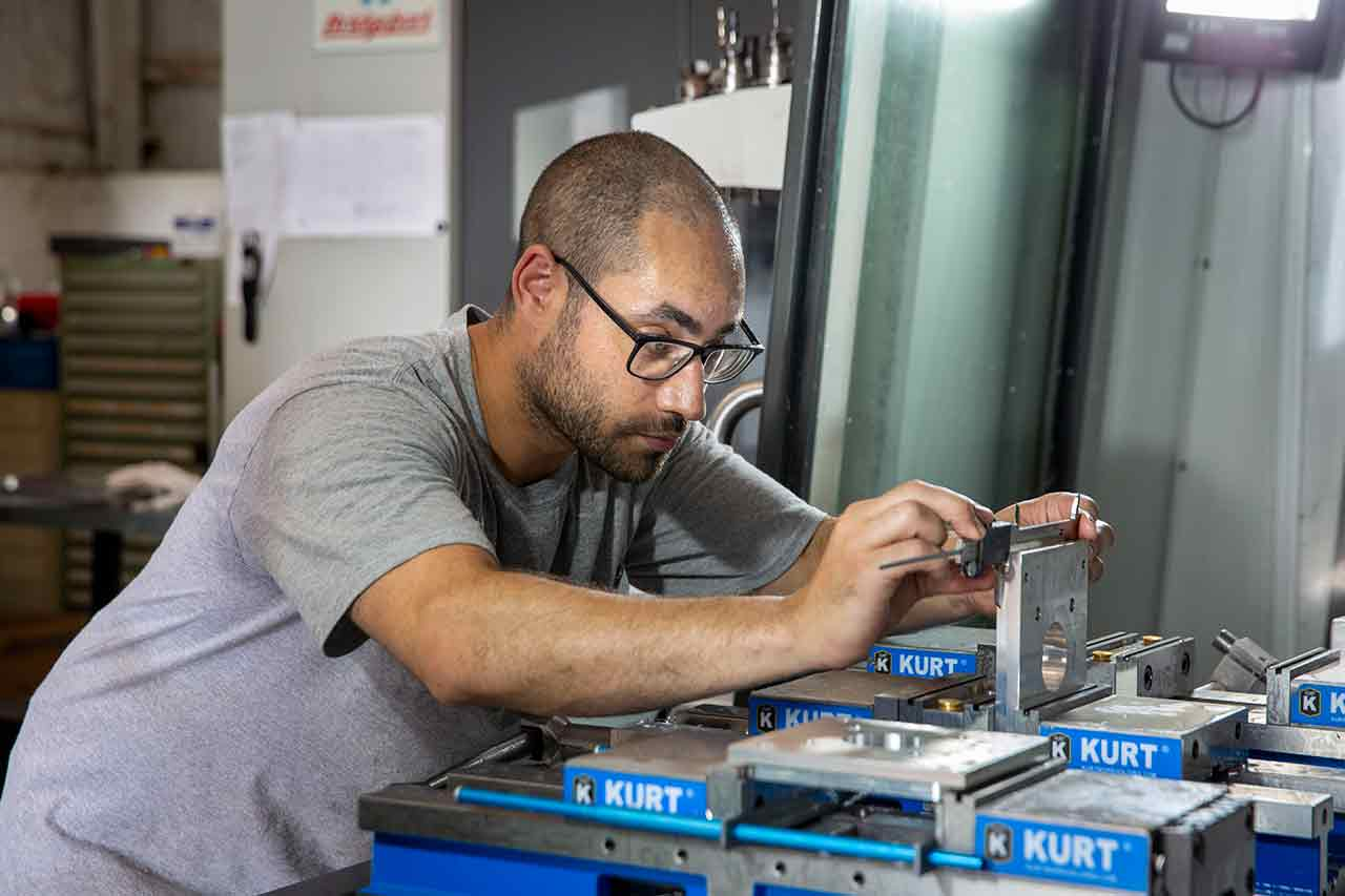 Picture of employee at Custom Metal Designs working on a metal design.