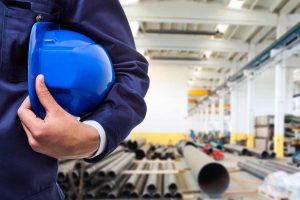 Picture of a man holding a hardhat while standing in a manufacturing warehouse